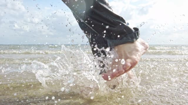 stockvideo's en b-roll-footage met man running in shallow water on a beach in the sun - tina terras michael walter
