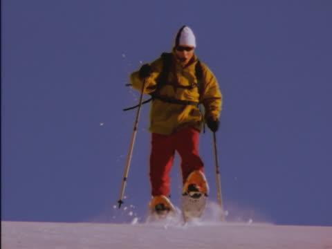 vídeos de stock e filmes b-roll de man running in snowshoes - bastão de esqui
