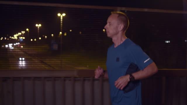 vídeos de stock, filmes e b-roll de slo mo t homem correndo na cidade à noite - camiseta