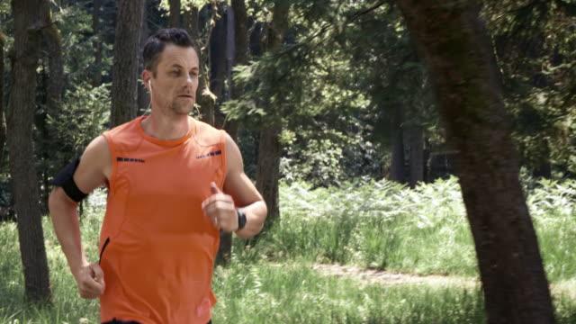 vídeos de stock, filmes e b-roll de slo mo ds homem correndo na floresta ouvir música - homens de idade mediana