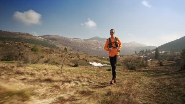 vídeos de stock e filmes b-roll de man running in the mountains on a sunny day in early spring - ensolarado