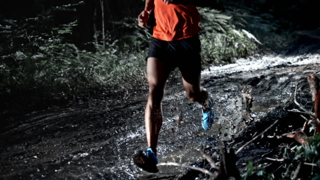 SLO MO DS Man running on a muddy forest trail at night