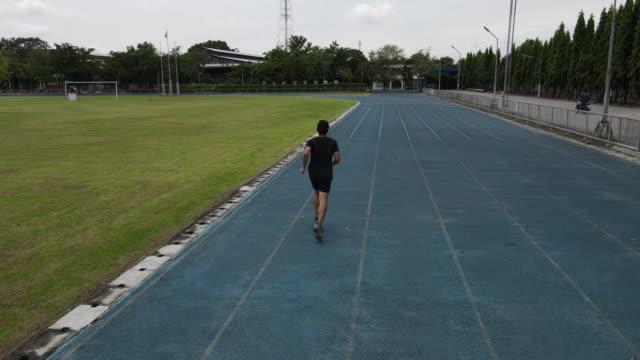 vídeos de stock, filmes e b-roll de um homem correndo em uma esteira de campo esportivo - revezamento