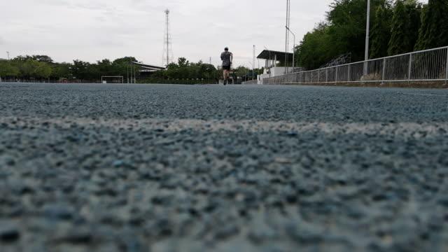 vídeos de stock, filmes e b-roll de um homem correndo em uma esteira de campo esportivo, câmera lenta - revezamento