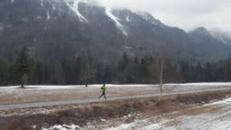 AERIAL Man running on a trail across a valley in winter under the snow covered mountain tops