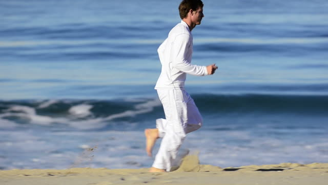 vidéos et rushes de  ms ts pan man running on beach / redondo beach, california, united states - seulement des jeunes hommes