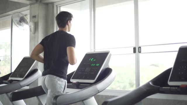 man running on gym treadmill