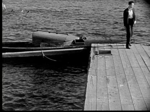 stockvideo's en b-roll-footage met 1925 ms b/w man running on jetty and boarding boat, rear view - 1925