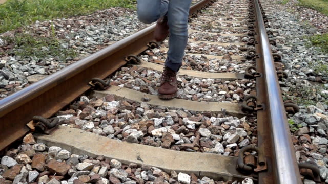 man running on rail track to camera 4k slow motion. - railroad track stock videos & royalty-free footage
