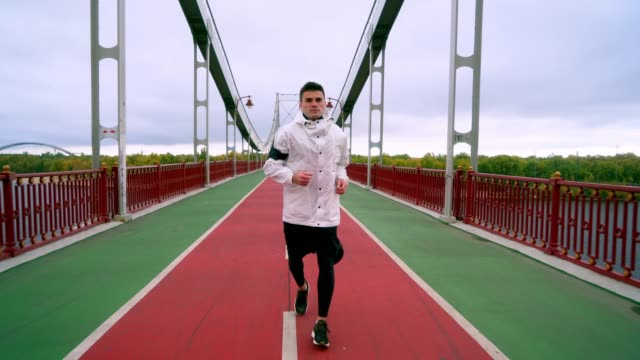 vídeos y material grabado en eventos de stock de hombre corriendo en el puente de kiev por la mañana - vista de frente