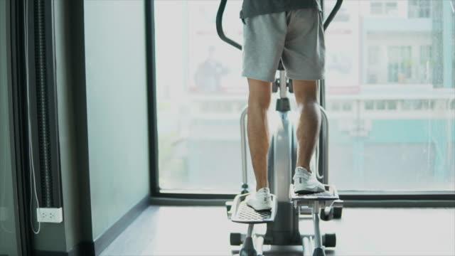 vídeos de stock, filmes e b-roll de homem que funciona na escada rolante na ginástica - esteira rolante aparelho de musculação