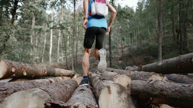 SLO MO DS Man running over a log stack in the forest