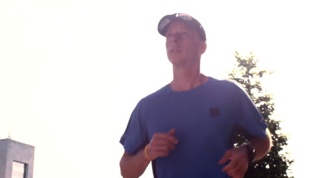 slo mo ts man running through a city street in sunshine - one mid adult man only stock videos & royalty-free footage