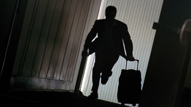 canted silhouette man running through jetway with wheeled baggage / phoenix, az - fluggastbrücke stock-videos und b-roll-filmmaterial