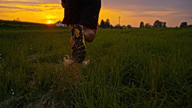 SLO MO Man Running Through Wet Grass