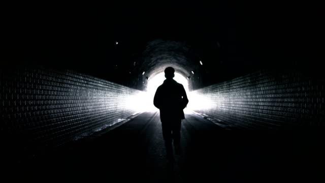 man running to light in dark tunnel - tunnel video stock e b–roll