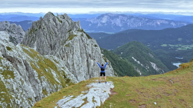 aerial man running to the mountain edge and raising his hands - top capo di vestiario video stock e b–roll