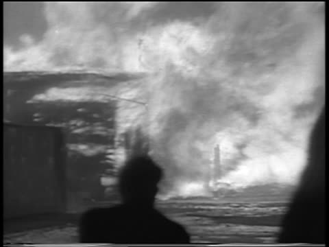 vidéos et rushes de silhouette man running toward building on fire in chicago stockyard / newsreel - 1934
