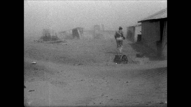 vídeos de stock e filmes b-roll de hd man running toward shelter ws farm windmill amp house roof in thick dust cloud fencing w/ desert land sand blowing - 1935