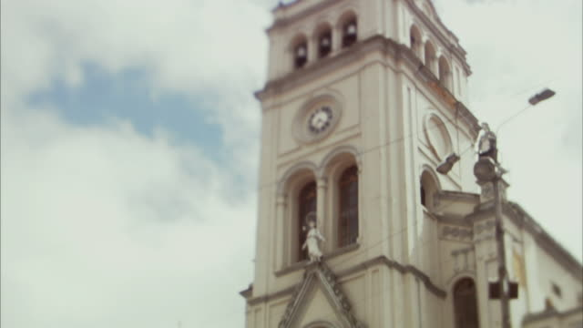 LA WS TD Man running up church stairs below clock tower / Bogota, Colombia