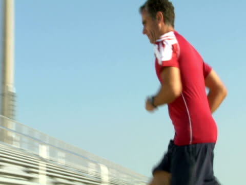 vidéos et rushes de ms,  la,  pan,  man running up on bleachers,  miami,  florida,  usa - 45 49 ans