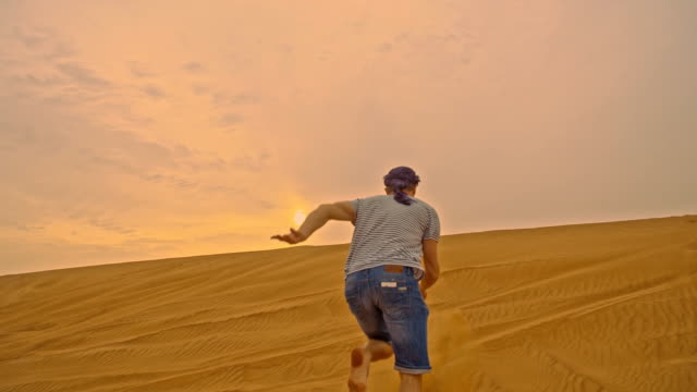 slo mo man running up the dune - adventure stock videos & royalty-free footage