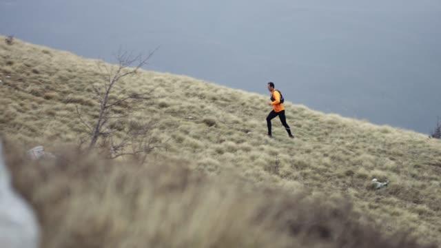 vidéos et rushes de homme qui court vers le haut de la pente de la montagne sur une journée nuageuse - qui monte