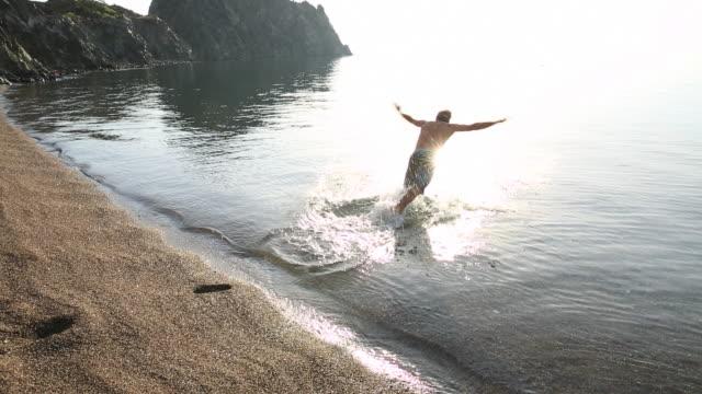 Man runs across beach and dives into sea