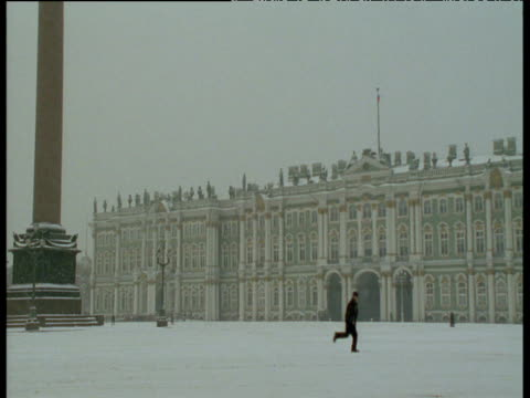 man runs across square in front of the winter palace (the hermitage museum). - sankt petersburg stock-videos und b-roll-filmmaterial