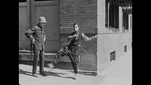 1920 man (buster keaton), runs and almost collides with smug policeman so he begins to dance - slapstick stock videos & royalty-free footage