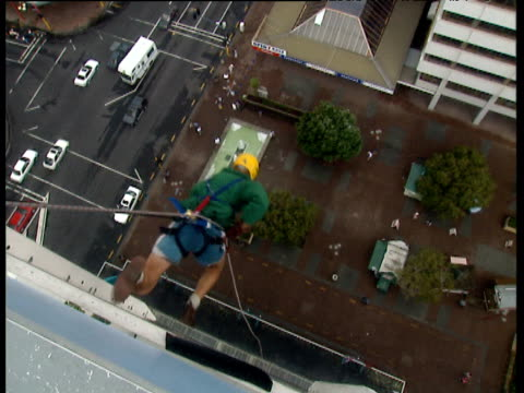 man runs and jumps off side of building then runs while abseiling down glass face to the ground attached by rope and harness auckland - アブセイリングをする点の映像素材/bロール