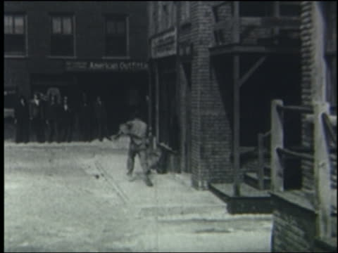 b/w 1923 man runs around corner, poses with mannequins on street; chasing crowd runs past him - 1923 stock-videos und b-roll-filmmaterial