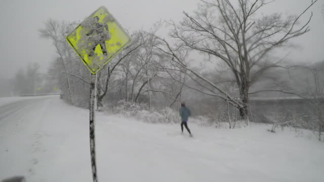 man läuft durch die kreuzung von zeichen im winter schneesturm - nur junge männer stock-videos und b-roll-filmmaterial