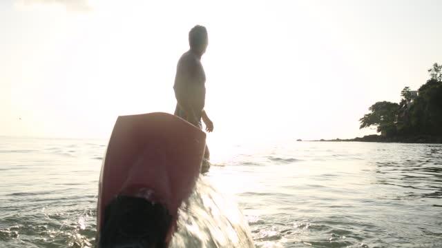 vídeos de stock e filmes b-roll de man runs in shallows besides snorkelling flippers - one mature man only