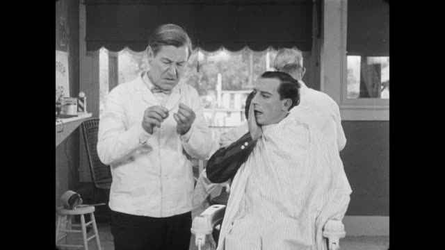 vidéos et rushes de 1928 a man (buster keaton) runs into old friend (marion byron), while at the barber shop - se raser