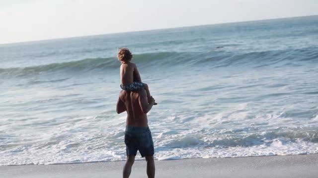 ms ts man runs into wavebreak with boy on shoulders / montezuma, puntarenas, costa rica - kelly mason videos stock videos & royalty-free footage