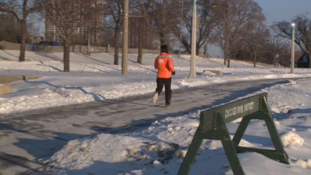 man runs on lakeshore path on january 30, 2019. - cold temperature stock videos & royalty-free footage
