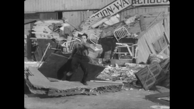 1928 A man (Buster Keaton) runs through a destroyed theater's stage door