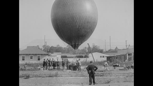 1923 man (buster keaton) runs to a hot air balloon being prepared for launch - 1923 stock videos & royalty-free footage