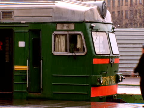 Man runs to catch green train in rain Russia