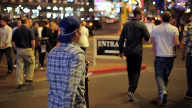 A man runs to catch up with his friends as they walk down the Las Vegas Strip.
