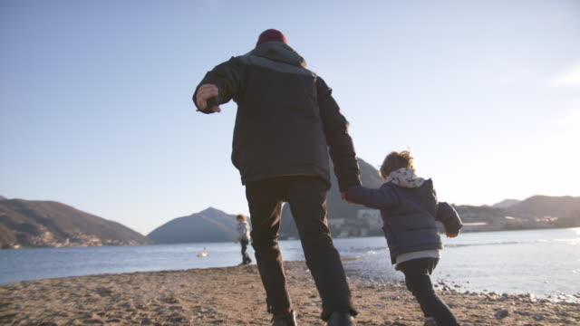 man runs with son along lakeside, view of sunset and mountains behind - open arms stock videos & royalty-free footage