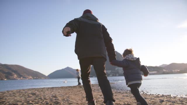 stockvideo's en b-roll-footage met de mens loopt met zoon langs lakeside, mening van zonsondergang en bergen achter - zoon