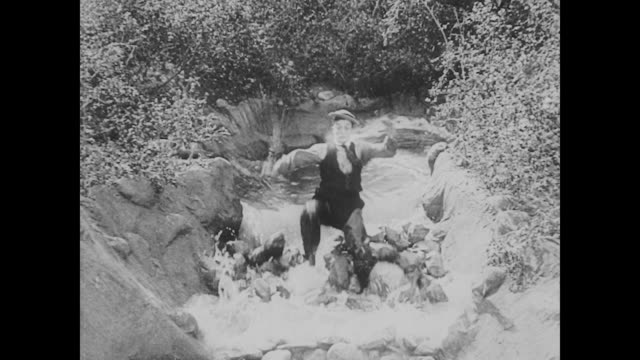 vídeos de stock, filmes e b-roll de 1923 man (buster keaton) rushes down river as damn breaks - 1923