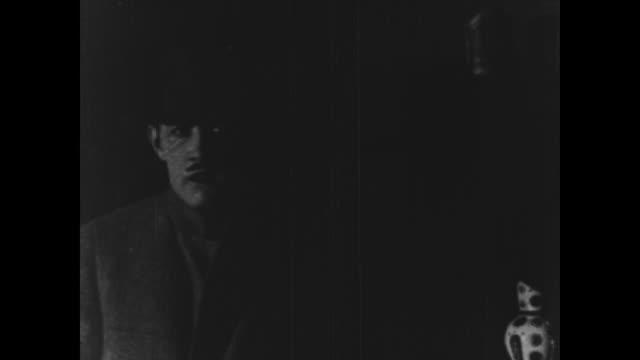 vidéos et rushes de 1925 man rushes into a darkened house and hides furtively in the shadows, peers out windows - cache