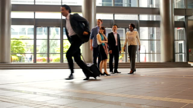 man rushes past group of business people in office lobby - checking the time stock videos & royalty-free footage