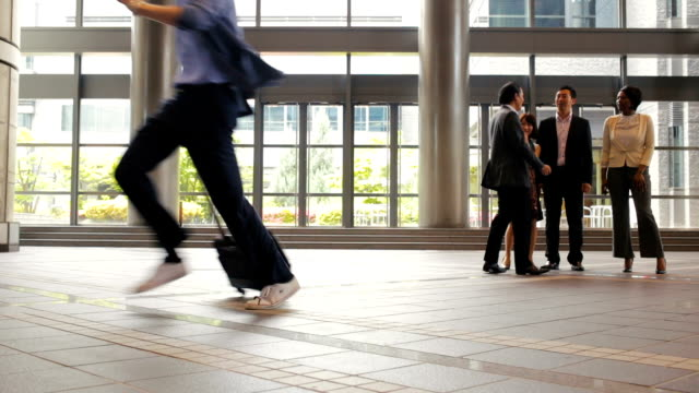 Man Rushes Past Group of Business People in Office Lobby