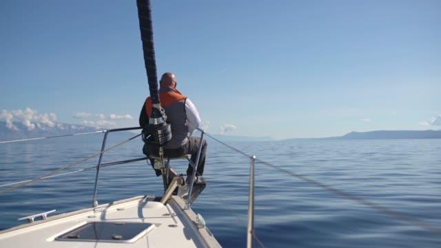 4 k mann segeln am schiffsbug auf sonnigen, ruhigen blauen ozean, zeitlupe - segelmannschaft stock-videos und b-roll-filmmaterial