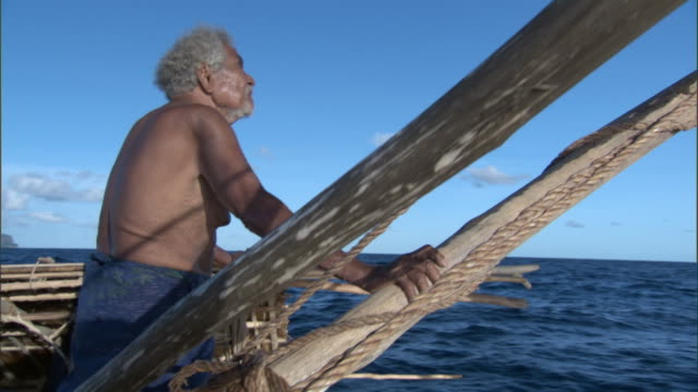 Man sails on outrigger canoe, Duff Islands, Solomon Islands