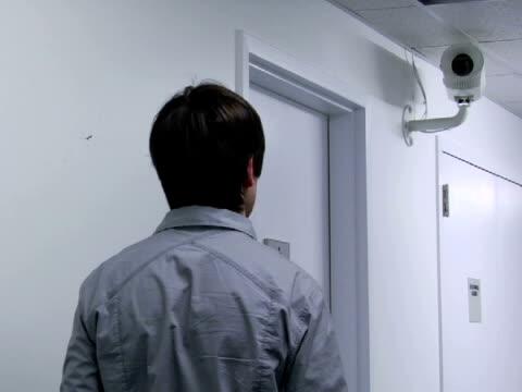 cu, man saluting to security camera in office, rear view - solo uomini di età media video stock e b–roll